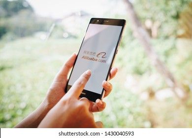 CHIANG MAI, THAILAND - JAN. 19,2019: Woman holding HUAWEI with alibaba apps on screen.Alibaba's the the world's biggest online commerce company. It's three main sites Taobao,Tmall and Alibaba.