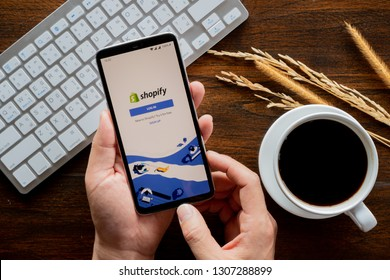 Chiang Mai / Thailand - jan 20 2019 : Hands hoding mobile with shopify screen, Coffee and keyboard on wood desk