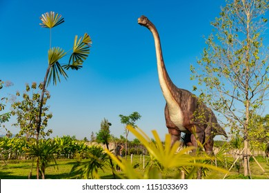 CHIANG MAI / THAILAND - JAN27.2018: One of the most popular tourist attractions of Thailand - dinosaur park in Hidden Village Chiang Mai / Young travel girl makes a photo dinosaur on nature background