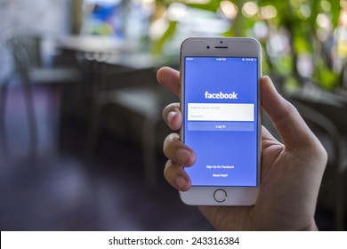 CHIANG MAI, THAILAND - JANUARY 02, 2015: A man trying to log in Facebook application using Apple iPhone 6. Facebook is largest and most popular social networking site in the world.