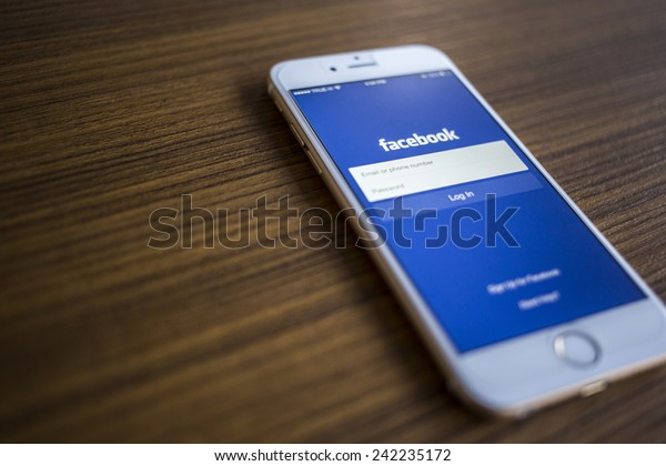 CHIANG MAI, THAILAND - JANUARY 02, 2015: Facebook Login page application on  Apple iPhone 6 and wood background. Facebook is largest and most popular social networking site in the world.