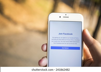CHIANG MAI, THAILAND - JANUARY 04, 2015: A man trying to join to Facebook application using Apple iPhone 6. Facebook is largest and most popular social networking site in the world.