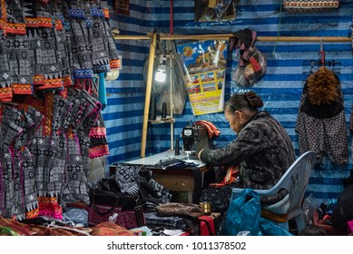 Chiang Mai, Thailand - January, 12, 2018 : Unidentified name woman sewing with a machine in native clothing store at Doi poy market Chiang Mai, Thailand