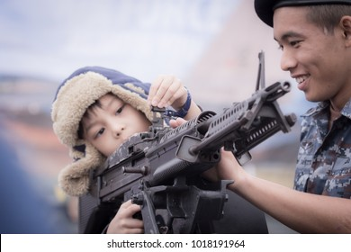 Chiang Mai, Thailand. January 13, 2018. Happiness Boy is Interested Aim The Machine Gun Which Displayed at the Children's Day Air Show Under Supervision of Soldier. in Chiang Mai Military Airport.