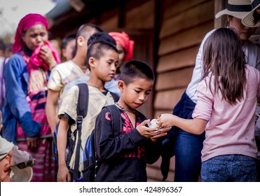 Chiang Mai Thailand -January,21,2016:A Girl from happiness family learn how to share the happiness by giving ice cream to a boy in remote area Karen village in remote area in Chiang Mai Thailand