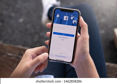 CHIANG MAI, THAILAND - JUL 16, 2019: Facebook social media app logo on log-in, sign-up registration page on mobile app screen on iPhone X (10) in person's hand working on e-commerce shopping business