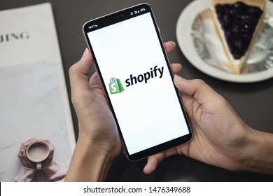 CHIANG MAI, THAILAND - Jul 17, 2019 : Male holds  Oneplus 6 with Shopify application on the screen in coffee shop. Shopify is an e-commerce platform for online stores - Image