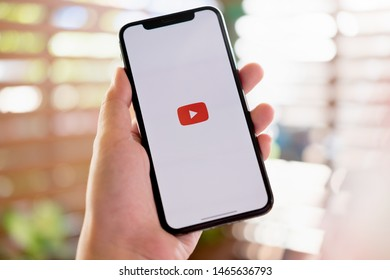 CHIANG MAI ,THAILAND JUL 27 2019 : Woman holding a iPhone X or iPhone 10 with social Internet service Youtube on the screen