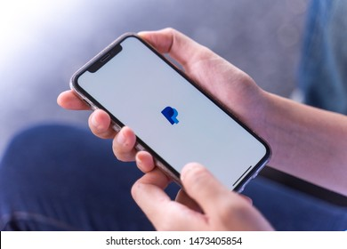 CHIANG MAI, THAILAND - Jul.27,2019: Woman holding Apple iPhone Xs with PayPal apps on screen. Paypal is an American online payment and banking company.