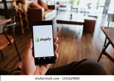 CHIANG MAI, THAILAND - JULY 07,2018: A Man holds Sony Mobile Phone with Shopify application on the screen in coffee shop. Shopify is an e-commerce platform for online stores
