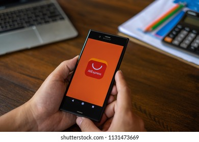 CHIANG MAI, THAILAND : JULY 09,2018 : A man holding Phone with Aliexpress application icon. AliExpress is e-commerce application from china.