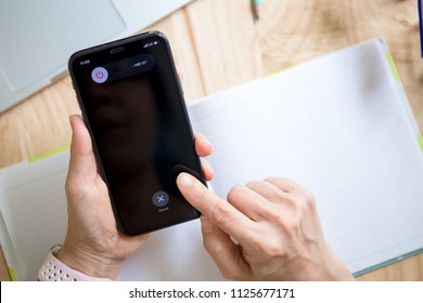 Chiang mai, Thailand - July 1,2018: Hand holding Apple iPhone x with slide to power off option on the screen.
