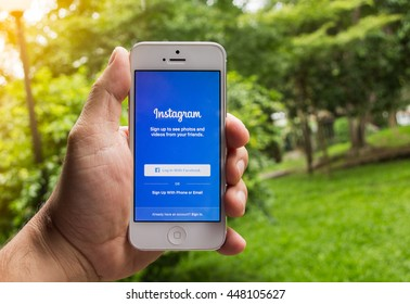 CHIANG MAI, THAILAND - July 6 ,2016 :man trying to login to Instagram using Apple iPhone 5. Instagram is largest and most popular  networking site in the world.garden sunset background.