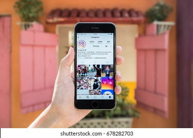 CHIANG MAI, THAILAND - July 8, 2017: A woman holds Apple iPhone 6S with Instagram application on the screen with latte hot, coffee cup on wood desk. Instagram is a photo-sharing app for smartphones.