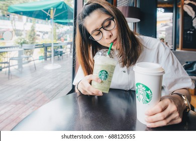 CHIANG MAI, THAILAND- July-24-2017 : Asian girl holding a cup of Venti size Starbucks coffee and Green tea latte frappuccino in Starbucks coffee shop.