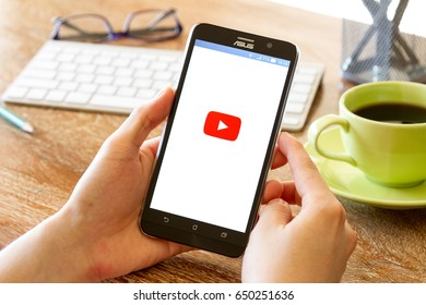 CHIANG MAI, THAILAND - JUN 16, 2016: man hand holding screen shot of Youtube application showing on Asus Zenfone 2 mobile phone. YouTube is the popular video sharing website.