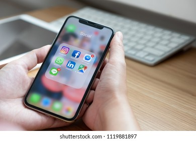 CHIANG MAI, THAILAND - JUN 22, 2018: Hand of man using iPhone X with icons of social media on screen, smartphone life style, smartphone era, smartphone in everyday life