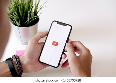 CHIANG MAI ,THAILAND JUN 22 2019 : Woman holding a iPhone Xs or iPhone 10 with social Internet service Youtube on the screenN