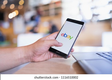 CHIANG MAI, THAILAND - June 03,2018: Man hands holding HUAWEI with eBay apps on the screen at coffee shop.eBay is one of the most popular ways to buy and sell goods and services on the internet.