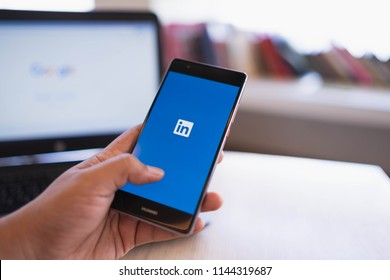 CHIANG MAI, THAILAND - June 03,2018: Man hands holding HUAWEI mobile phone with Linkedin application on the screen. Linkedin is a business and employment oriented social networking service.
