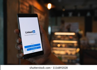 CHIANG MAI, THAILAND - June 09,2018: Man hands holding HUAWEI mobile phone with Linkedin application on the screen. Linkedin is a business and employment oriented social networking service.