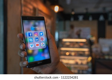 CHIANG MAI, THAILAND - June 09,2018: Man holding HUAWEI with icons of social media on the screen. Social media are most popular tool. Smartphone lifestyle. Starting social media app.