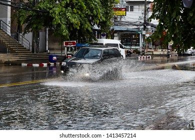 CHIANG MAI , THAILAND - JUNE 1,2019: Car driving on wet road when  flood water with splashing water in the evening. Selective Focus.