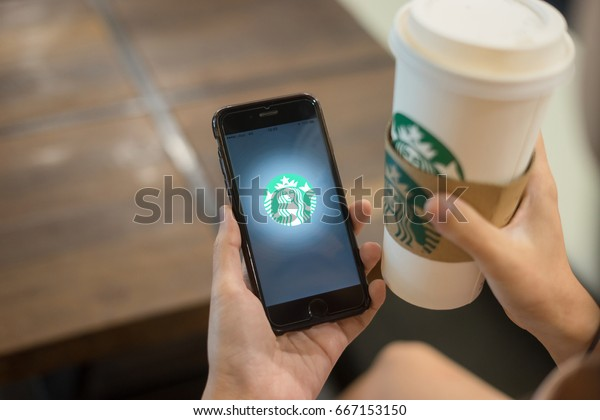 Chiang Mai, Thailand June 18, 2017,Hand holding smart phone opening online menu page of Starbucks website, Starbucks coffee cup on hand background,Starbucks coffee shop.