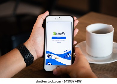 Chiang Mai / Thailand - June 22 2019 : Hands hoding mobile with shopify screen in coffee shop.