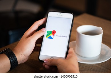 Chiang Mai / Thailand - June 22 2019 : Hands holding mobile with google maps screen in coffee shop.