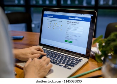 Chiang mai, Thailand - June 25,2018: Facebook login page in a computer screen. Woman holding a laptop on her knees while type on the keyboard.