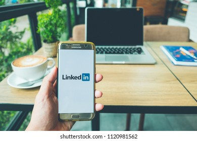 CHIANG MAI, THAILAND - June 26,2018: A Man holds Samsung Galaxy S7 edge Mobile Phone with Linkedin application on the screen in coffee shop. Linkedin in a business and employment-oriented service