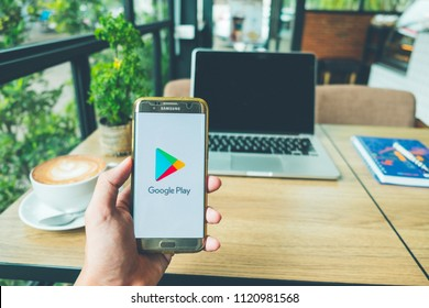 CHIANG MAI, THAILAND - June 26,2018: A Man holds Samsung Galaxy S7 edge Mobile Phone with Google Play application on the screen in coffee shop. Google Play is an app store for the Android system