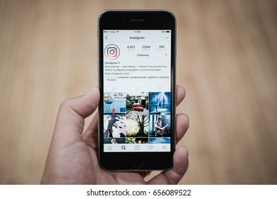 CHIANG MAI, THAILAND - JUNE 4, 2017: A woman holds Apple iPhone 6S with Instagram application on the screen with latte hot, coffee cup on wood desk. Instagram is a photo-sharing app for smartphones.