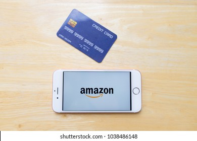 CHIANG MAI, THAILAND - Mar 02,2018: Apple iPhone 6S Rose Gold with Amazon apps and credit card on wooden table. Online shopping via smartphone app concept.