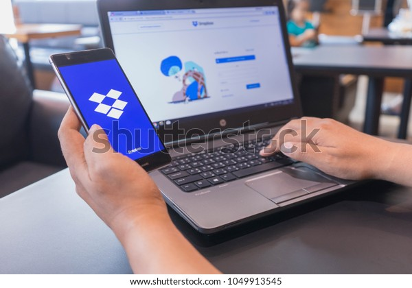 CHIANG MAI, THAILAND - Mar 18,2018: Man hands holding HUAWEI with Dropbox on the screen. Dropbox is a service that gives you access to images, documents and videos online from anywhere.