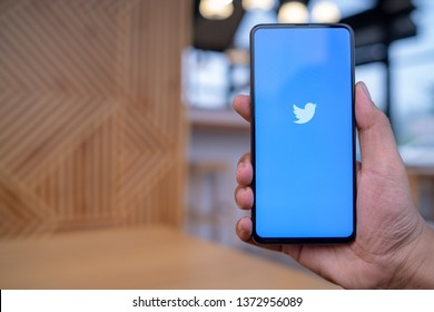 CHIANG MAI, THAILAND - Mar. 23,2019: Man holding Xiaomi Mi Mix 3 with Twitter app on the screen.Twitter is an online news and social networking service where users post and interact with messages.