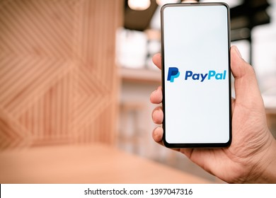 CHIANG MAI, THAILAND - Mar. 23,2019: Man holding Xiaomi Mi Mix 3 with PayPal apps on the screen. PayPal is an online electronic payment system.