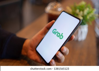 CHIANG MAI, THAILAND - Mar. 24,2019: Man holding Xiaomi Mi Mix 3 with Grab apps on screen. Grab is smartphone app all-in-one transport booking in South-East Asia.