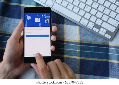CHIANG MAI, THAILAND - Mar 28,2018: Man hands holding HUAWEI with facebook app on the screen. Facebook is a popular free social  media are used for information sharing and networking.