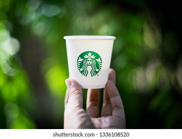 CHIANG MAI, THAILAND - MAR 5, 2019: hand holding starbucks paper cup with green blurred bokeh background, analysts think starbucks might launch cannabis-infused drinks first