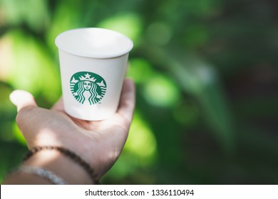 CHIANG MAI, THAILAND - MAR 5, 2019: hand holding starbucks paper cup with green bokeh background, starbucks is global coffee company that analysts think might launch cannabis-infused drinks first