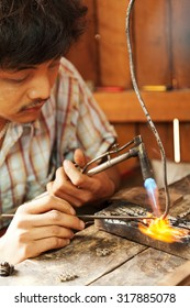 Chiang Mai, Thailand - March 02, 2011 : Young Thai man making silver jewelry