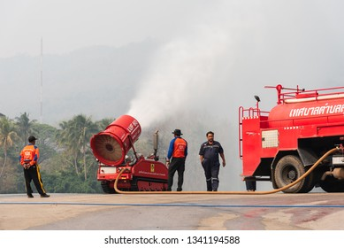 "CHIANG MAI, THAILAND - March 16 , 2019: Unidentified Firemen sprinkled water on the sky to reduce pollution from the air at the large lake called ""Ang Kaew"" in Chiang Mai University on March 16, 2019."