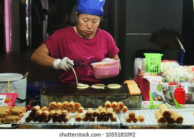 Chiang Mai, Thailand - March 26, 2018: Woman cooking and selling sweet street food in a local night market