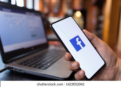 CHIANG MAI, THAILAND - May 01,2019: Man holding Xiaomi Mi Mix3 with facebook app on the screen. Facebook is a popular free social media are used for information sharing and networking.