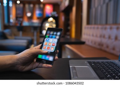 CHIANG MAI, THAILAND - May 05,2018: Man holding HUAWEI with icons of E-commerce and online shopping on screen.smartphone lifestyle,e-commerce app concept.