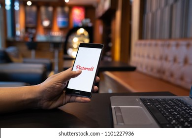 CHIANG MAI, THAILAND - May 05,2018: Man hands holding HUAWEI mobile phone with Pinterest apps login on screen. Pinterest is an online pinboard that allows people to pin their interesting things.