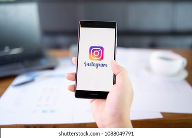 CHIANG MAI, THAILAND - May 06,2018: Man hands holding HUAWEI with Instagram application on the screen. Instagram is a popular online social networking service.