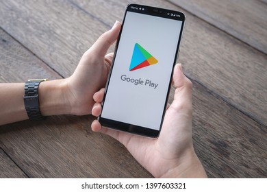 CHIANG MAI, THAILAND - May 11,2019 : A Man holds Oneplus 6 with Google Play application on the screen in coffee shop. Google Play is an app store for the ios system